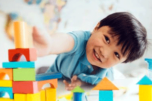 Preschool daycare program with kid playing with building blocks