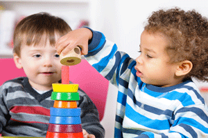 Toddler care program with two kids stacking toys